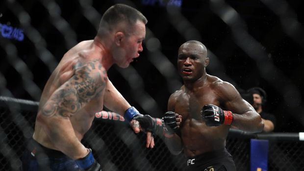 LAS VEGAS, NEVADA - DECEMBER 14: Colby Covington (L) falls back from a punch by UFC welterweight champion Kamaru Usman in the fifth round of their welterweight title fight during UFC 245 at T-Mobile Arena on December 14, 2019 in Las Vegas, Nevada. Usman retained his title with a fifth-round TKO.   Steve Marcus/Getty Images/AFP