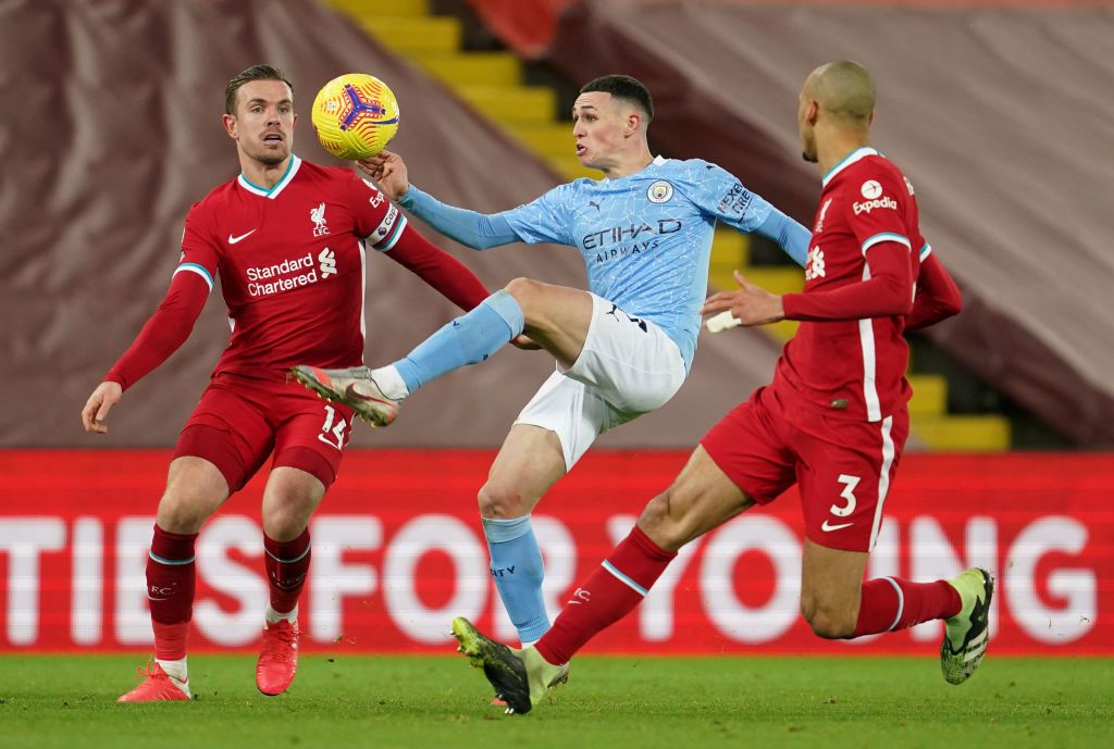 LIVERPOOL, ENGLAND - FEBRUARY 07: Phil Foden of Manchester City battles for possession with (L - R) Jordan Henderson and Fabinho of Liverpool during the Premier League match between Liverpool and Manchester City at Anfield on February 07, 2021 in Liverpool, England. Sporting stadiums around the UK remain under strict restrictions due to the Coronavirus Pandemic as Government social distancing laws prohibit fans inside venues resulting in games being played behind closed doors (Photo by Jon Super - Pool/Getty Images)