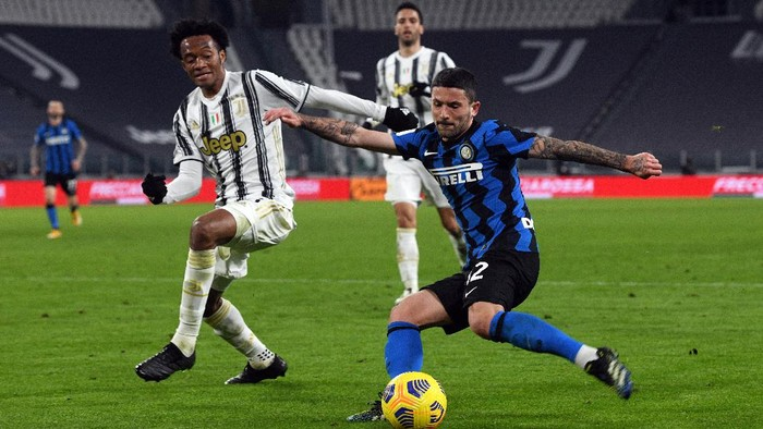 TURIN, ITALY - FEBRUARY 09: Stefano Sensi of FC Internazionale is closed down by Juan Cuadrado of Juventus during the Coppa Italia semi-final Juventus and FC Internazionale at Allianz Stadium on February 09, 2021 in Turin, Italy. Sporting stadiums around Italy remain under strict restrictions due to the Coronavirus Pandemic as Government social distancing laws prohibit fans inside venues resulting in games being played behind closed doors. (Photo by Chris Ricco/Getty Images)