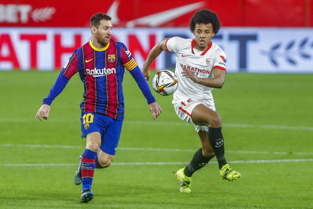 Barcelona's Lionel Messi, left, vies for the ball with Sevilla's Jules Kounde during a Spanish Copa del Rey semifinal soccer match between Sevilla and FC Barcelona at Ramon Sanchez Pizjuan stadium in Seville , Spain, Wednesday, Feb. 10, 2021. (AP Photo/Angel Fernandez)