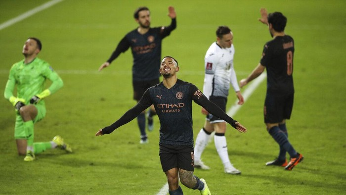 Manchester Citys Gabriel Jesus celebrates scoring against Swansea City during the English FA Cup fifth round soccer match at Liberty Stadium, Swansea, Wales, Wednesday Feb. 10, 2021. (Nick Potts/PA via AP)