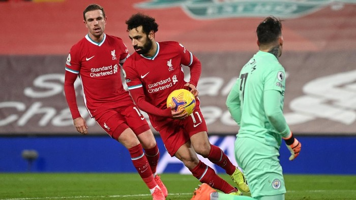 LIVERPOOL, ENGLAND - FEBRUARY 07: Mohamed Salah of Liverpool is congratulated by team mate Jordan Henderson as he collects the ball after scoring their sides first goal from the penalty spot during the Premier League match between Liverpool and Manchester City at Anfield on February 07, 2021 in Liverpool, England. Sporting stadiums around the UK remain under strict restrictions due to the Coronavirus Pandemic as Government social distancing laws prohibit fans inside venues resulting in games being played behind closed doors. (Photo by Laurence Griffiths/Getty Images)