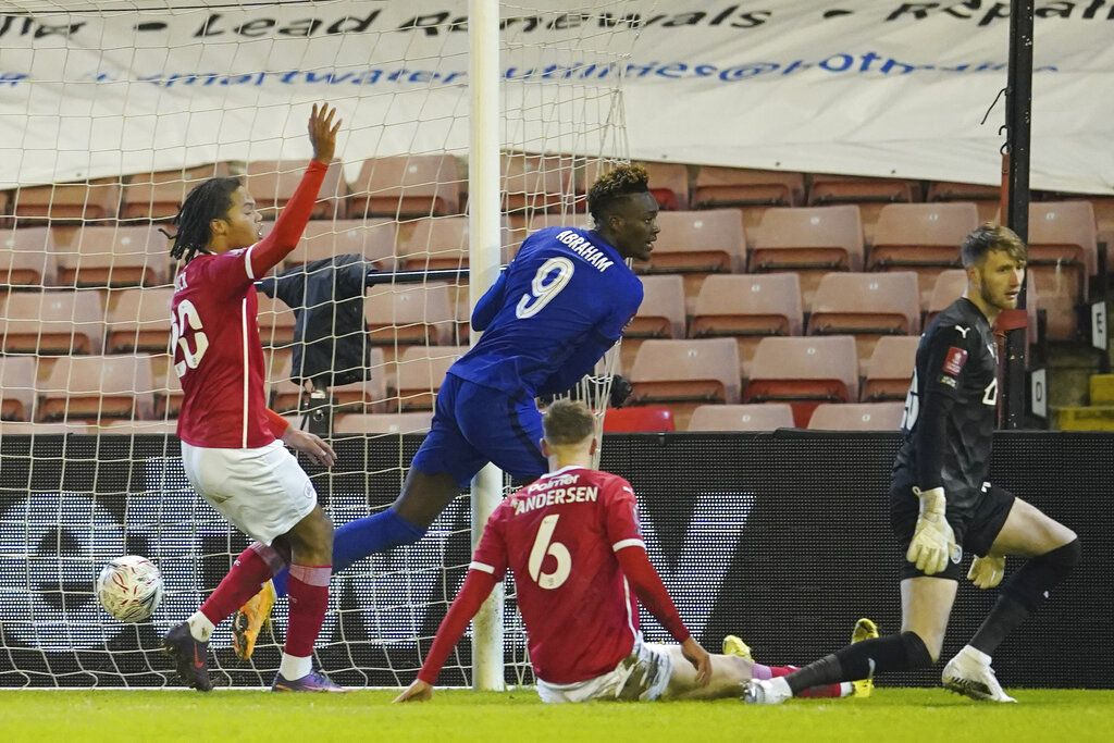 Chelsea's Tammy Abraham, centre, scores the opening goal during the English FA Cup fifth round soccer match between Barnsley and Chelsea at the Oakwell Stadium in Barnsley, England,Thursday Feb. 11, 2021. (AP Photo/Dave Thompson, Pool)