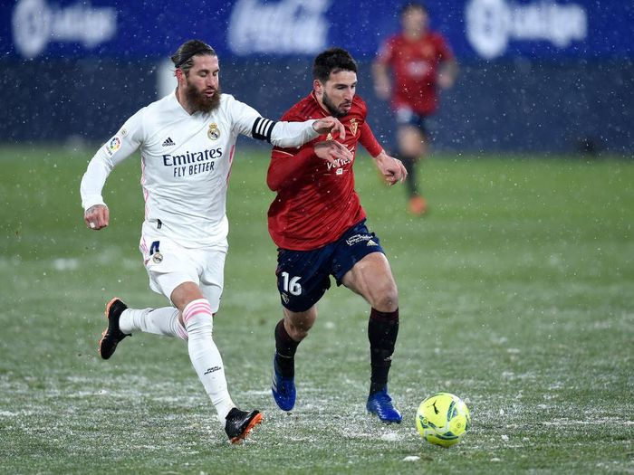 PAMPLONA, SPAIN - JANUARY 09: Jonathan Calleri of Osasuna is challenged by Sergio Ramos of Real Madrid during the La Liga Santander match between C.A. Osasuna and Real Madrid at Estadio El Sadar on January 09, 2021 in Pamplona, Spain. Sporting stadiums around Spain remain under strict restrictions due to the Coronavirus Pandemic as Government social distancing laws prohibit fans inside venues resulting in games being played behind closed doors. (Photo by Juan Manuel Serrano Arce/Getty Images)