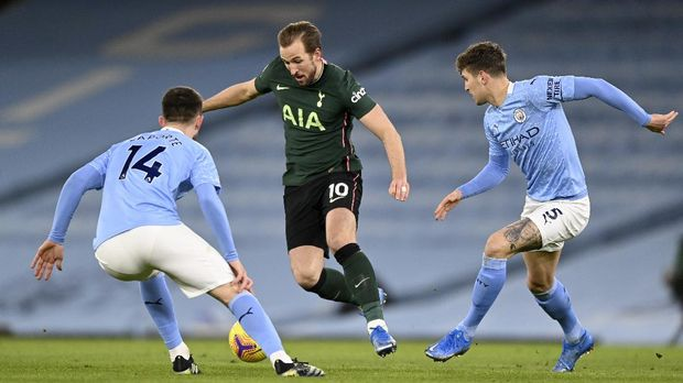 Tottenham's Harry Kane tries to drive the ball past Manchester City's Aymeric Laporte, left, and John Stones, right, during the English Premier League soccer match between Manchester City and Tottenham Hotspur at Etihad Stadium, Manchester, England, Saturday, Feb. 13, 2021. (Shaun Botterhill/Pool via AP)