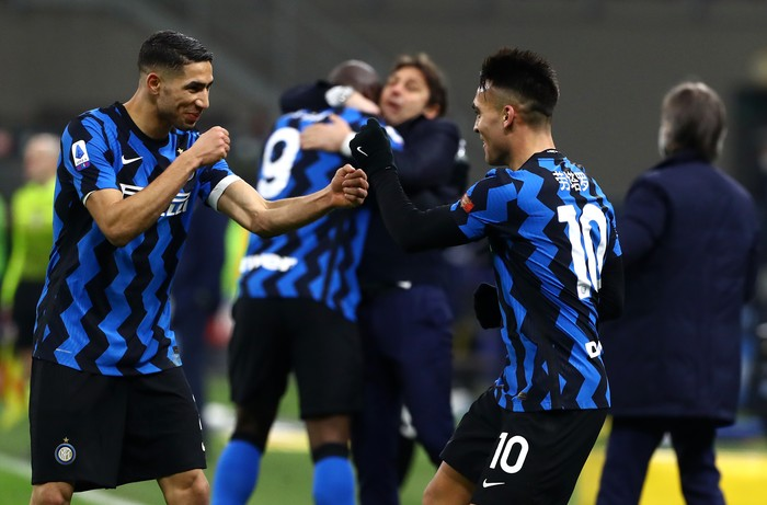 MILAN, ITALY - FEBRUARY 14: Lautaro Martinez of FC Internazionale celebrates with team mate Achraf Hakimi after scoring their side's third goal during the Serie A match between FC Internazionale  and SS Lazio at Stadio Giuseppe Meazza on February 14, 2021 in Milan, Italy. Sporting stadiums around Italy remain under strict restrictions due to the Coronavirus Pandemic as Government social distancing laws prohibit fans inside venues resulting in games being played behind closed doors. (Photo by Marco Luzzani/Getty Images)