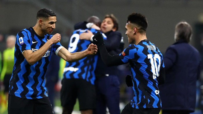 MILAN, ITALY - FEBRUARY 14: Lautaro Martinez of FC Internazionale celebrates with team mate Achraf Hakimi after scoring their sides third goal during the Serie A match between FC Internazionale  and SS Lazio at Stadio Giuseppe Meazza on February 14, 2021 in Milan, Italy. Sporting stadiums around Italy remain under strict restrictions due to the Coronavirus Pandemic as Government social distancing laws prohibit fans inside venues resulting in games being played behind closed doors. (Photo by Marco Luzzani/Getty Images)