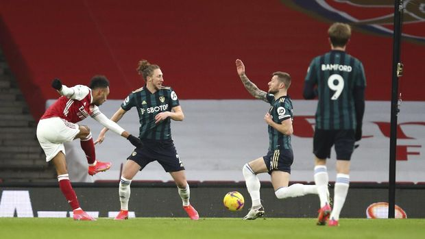 Arsenal's Pierre-Emerick Aubameyang, left, scores his side's opening goal during the English Premier League soccer match between Arsenal and Leeds United at the Emirates stadium in London, England, Sunday, Feb. 14, 2021. (Julian Finney/Pool via AP)