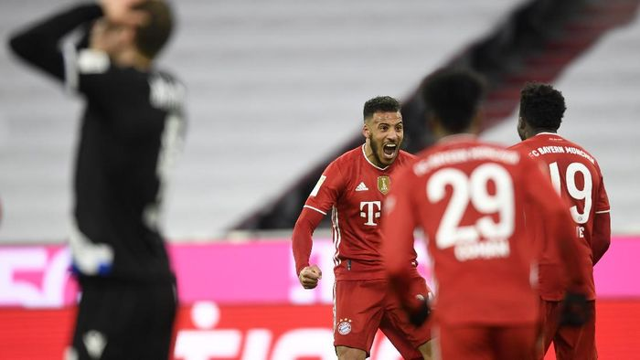 Bayerns Corentin Tolisso, left, Alphonso Davies, right rear, celebrate the third goal against Arminia during a German Bundesliga soccer match between Bayern Munich and Arminia Bielefeld at the Allianz Arena in Munich, Germany, Monday, Feb. 15, 2021. (AP Photo/Andreas Schaad, Pool)