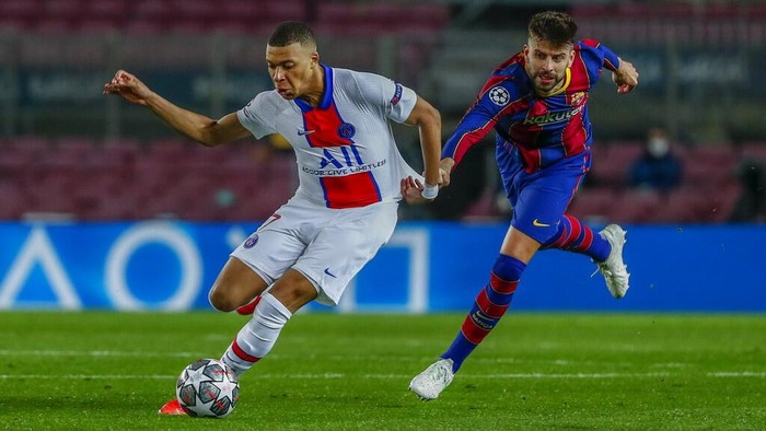 Barcelonas Gerard Pique, right, tries to stop PSGs Kylian Mbappe during the Champions League round of 16, first leg soccer match between FC Barcelona and Paris Saint-Germain at the Camp Nou stadium in Barcelona, Spain, Tuesday, Feb. 16, 2021. (AP Photo/Joan Monfort)