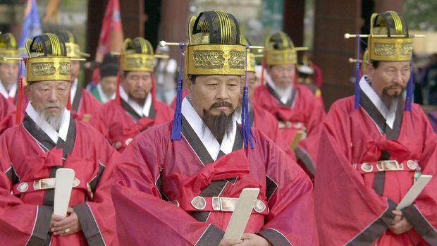 People dressed in traditional Joseon dynasty uniforms attend a Cultural Properties Administration's reappearance ceremony in Changgyeong Palace in Seoul on 21 October 2001.  This is an annual cultural ceremony to show traditional loyalty to the king in days past. AFP PHOTO (Photo by KIM JAE-HWAN / AFP)