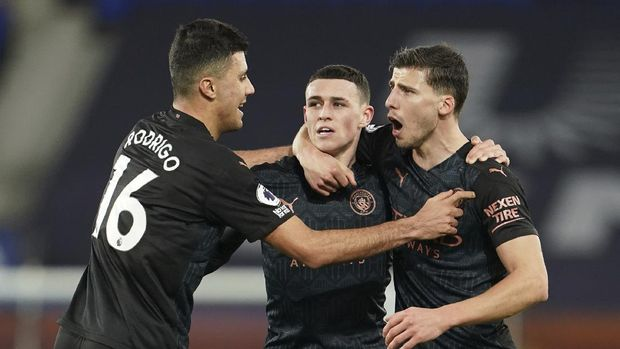 Manchester City's Phil Foden, center, celebrates scoring his side's first goal during the English Premier League soccer match between Everton and Manchester City at Goodison Park stadium, in Liverpool, England, Wednesday, Feb. 17, 2021. (Jon Super/Pool via AP)