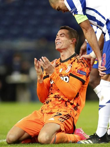 Porto's Pepe watches as Juventus' Cristiano Ronaldo gestures on the ground during the Champions League round of 16, first leg, soccer match between FC Porto and Juventus at the Dragao stadium in Porto, Portugal, Wednesday, Feb. 17, 2021. (AP Photo/Luis Vieira)
