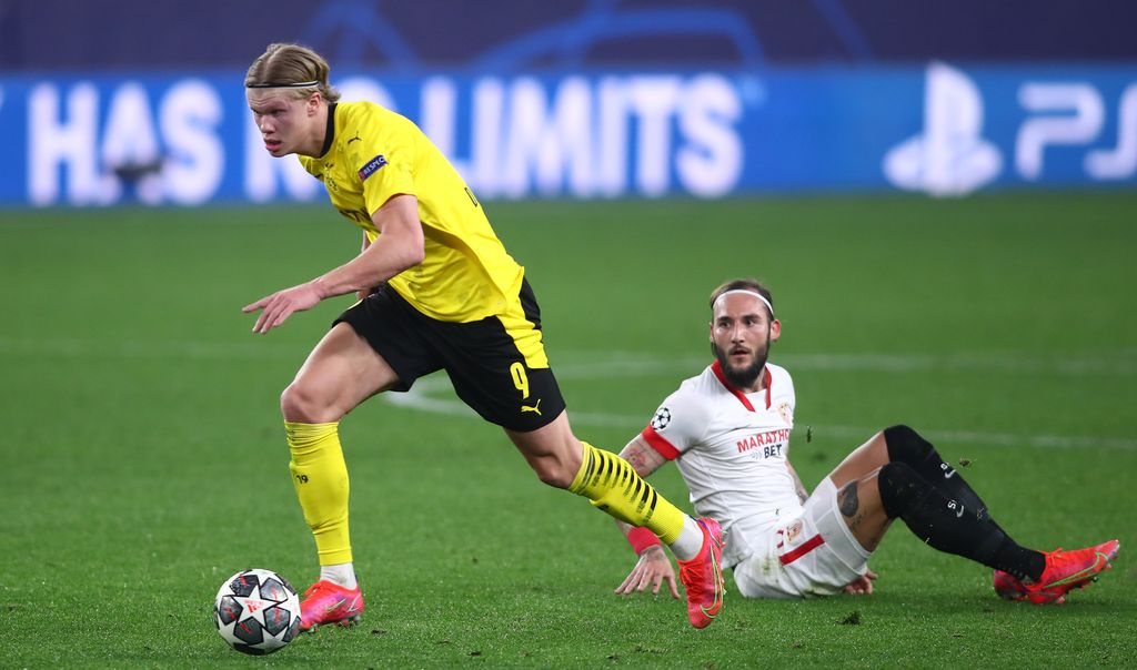 SEVILLE, SPAIN - FEBRUARY 17: Erling Haaland of Borussia Dortmund gets away from Nemanja Gudelj of Sevilla during the UEFA Champions League Round of 16 match between Sevilla FC and Borussia Dortmund at Estadio Ramon Sanchez Pizjuan on February 17, 2021 in Seville, Spain. Sporting stadiums around Spain remain under strict restrictions due to the Coronavirus Pandemic as Government social distancing laws prohibit fans inside venues resulting in games being played behind closed doors. (Photo by Fran Santiago/Getty Images)