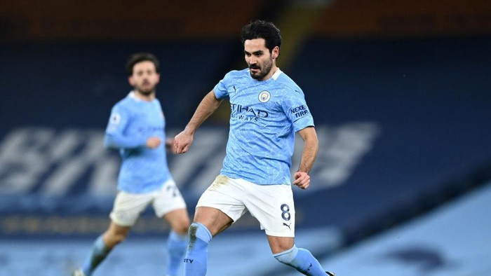 MANCHESTER, ENGLAND - FEBRUARY 13:  Ilkay Gundogan of Manchester City passes the ball during the Premier League match between Manchester City and Tottenham Hotspur at Etihad Stadium on February 13, 2021 in Manchester, England. Sporting stadiums around the UK remain under strict restrictions due to the Coronavirus Pandemic as Government social distancing laws prohibit fans inside venues resulting in games being played behind closed doors. (Photo by Shaun Botterill/Getty Images)