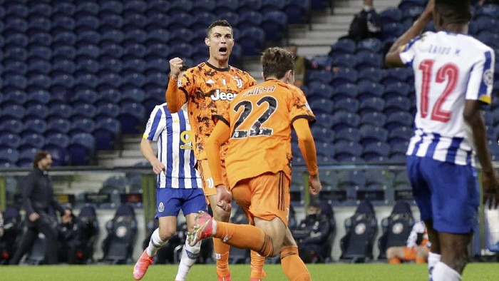 Juventus Cristiano Ronaldo celebrates after teammate Federico Chiesa, center, scored their sides first goal during the Champions League round of 16, first leg, soccer match between FC Porto and Juventus at the Dragao stadium in Porto, Portugal, Wednesday, Feb. 17, 2021. (AP Photo/Luis Vieira)