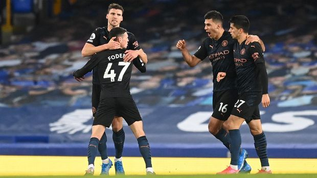 LIVERPOOL, ENGLAND - FEBRUARY 17: Phil Foden of Manchester City celebrates with team mates (L - R) Ruben Dias, Rodrigo and Joao Cancelo after scoring their side's first goal during the Premier League match between Everton and Manchester City at Goodison Park on February 17, 2021 in Liverpool, England. Sporting stadiums around the UK remain under strict restrictions due to the Coronavirus Pandemic as Government social distancing laws prohibit fans inside venues resulting in games being played behind closed doors. (Photo by Michael Regan/Getty Images)