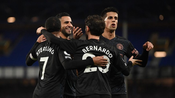 LIVERPOOL, ENGLAND - FEBRUARY 17: Bernardo Silva of Manchester City celebrates with team mates (L - R) Raheem Sterling, Riyad Mahrez, Joao Cancelo after scoring their sides third goal during the Premier League match between Everton and Manchester City at Goodison Park on February 17, 2021 in Liverpool, England. Sporting stadiums around the UK remain under strict restrictions due to the Coronavirus Pandemic as Government social distancing laws prohibit fans inside venues resulting in games being played behind closed doors. (Photo by Michael Regan/Getty Images)