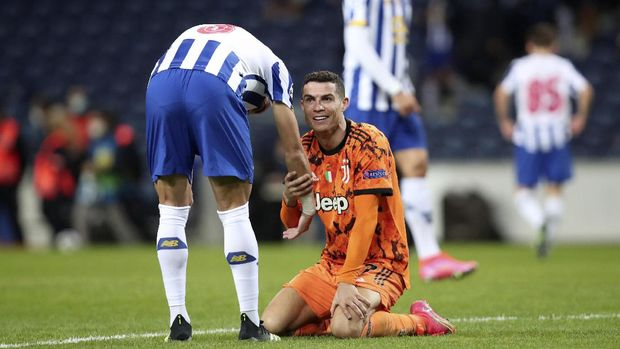 Porto's Pepe, left, helps Juventus' Cristiano Ronaldo gets back on his feet during the Champions League round of 16, first leg, soccer match between FC Porto and Juventus at the Dragao stadium in Porto, Portugal, Wednesday, Feb. 17, 2021. (AP Photo/Luis Vieira)