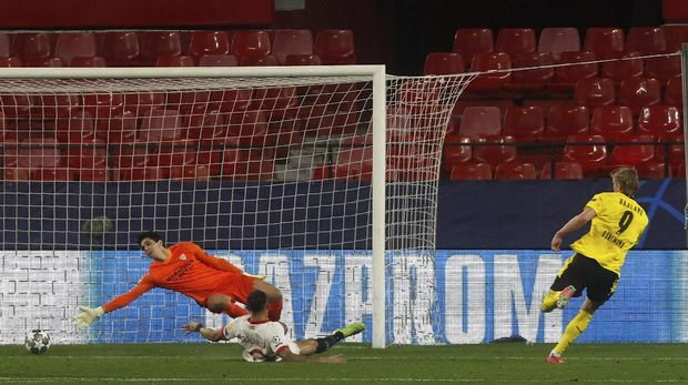Dortmund's Erling Haaland, right, scores his side's third goal during the Champions League, round of 16, first leg soccer match between Sevilla and Borussia Dortmund at the Ramon Sanchez Pizjuan stadium in Seville, Spain, Wednesday, Feb. 17, 2021. (AP Photo/Angel Fernandez)