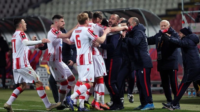 BELGRADE, SERBIA - FEBRUARY 18: Guelor Kanga of Crvena Zvezda (C) celebrates after scoring their sides first goal with Dejan Stankovic, manager of Crvena Zvezda during the UEFA Europa League Round of 32 match between Crvena Zvezda and AC Milan at Rajko Mitic Stadium on February 18, 2021 in Belgrade, Serbia. Sporting stadiums around Serbia remain under strict restrictions due to the Coronavirus Pandemic as Government social distancing laws prohibit fans inside venues resulting in games being played behind closed doors. (Photo by Srdjan Stevanovic/Getty Images)