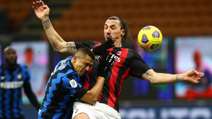 MILAN, ITALY - JANUARY 26:  Zlatan Ibrahimovic (R) of AC Milan competes for the ball with Alexis Sanchez (L) of Internazionale during the Coppa Italia match between FC Internazionale and AC Milan at Stadio Giuseppe Meazza on January 26, 2021 in Milan, Italy. Sporting stadiums around Italy remain under strict restrictions due to the Coronavirus Pandemic as Government social distancing laws prohibit fans inside venues resulting in games being played behind closed doors.  (Photo by Marco Luzzani/Getty Images)