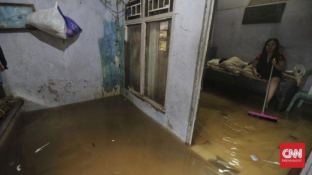 Warga berjalan melintasi banjir yang merendam kawasan  Pancoran Barat Jakarta, Jumat, 19 Februari 2021. Sejumlah kawasan di Jakarta terendam banjir akibat curah hujan yang tinggi.  CNN Indonesia/Adhi Wicaksono