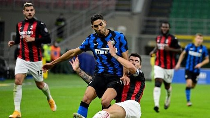 Inter Milans Moroccan defender Achraf Hakimi (L) fights for the ball with AC Milans Italian defender Alessio Romagnoli during the Italian Serie A football match between Inter Milan and AC Milan at the San Siro stadium in Milan on October 17, 2020. (Photo by Miguel MEDINA / AFP)