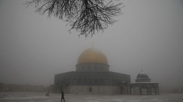 A man walks near the Dome of the Rock Mosque in the Al Aqsa Mosque compound during a snowy morning in Jerusalem's Old City, Thursday, Feb. 18, 2021. (AP Photo/Mahmoud Illean)