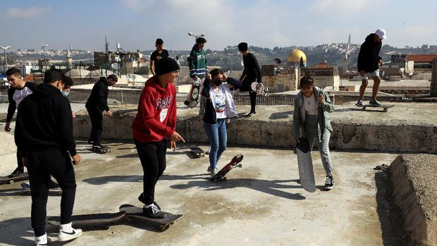 The Dome of the Rock located on the compound known to Muslims as Noble Sanctuary and to Jews as Temple Mount is seen in the background as Palestinian youths skateboard on rooftops, as Israel partially lifts its third national lockdown to fight the coronavirus disease (COVID-19) crisis, in Jerusalem's Old City February 7, 2021. Picture taken February 7, 2021. REUTERS/Ammar Awad