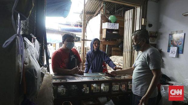 Tjan Kee Liong, kakak Tjan Kee Beng, saat melayani pembeli di toko mereka. Kebanyakan pelanggan lebih menyukai tembakau mole dan kretek.