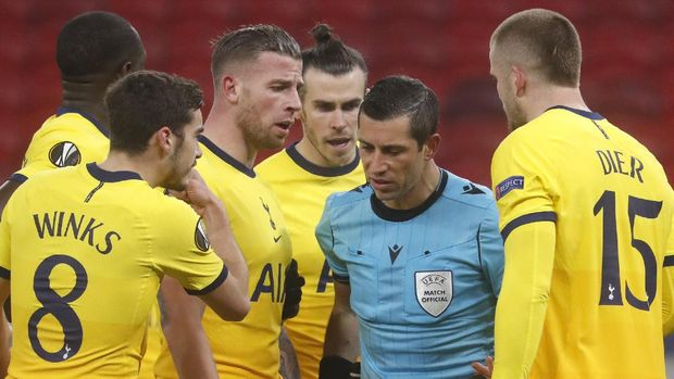Tottenham's players argue with the referee after he awarded a penalty shot against their team during the Europa League round of 32, first leg, soccer match between Wolfsberger AC and Tottenham Hotspur at the Puskas Arena stadium in Budapest, Hungary, Thursday, Feb. 18, 2021. (AP Photo/Laszlo Balogh)