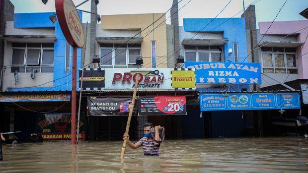 Warga berjalan menerobos banjir di kawasan Regency, Pasar Kemis, Kabupaten Tangerang, Banten, Sabtu (20/2/2021). Hujan deras yang mengguyur sejak Sabtu (20/2) dini hari menyebabkan kawasan tersebut terendam banjir hingga 1,5 meter. ANTARA FOTO/Fauzan/rwa.