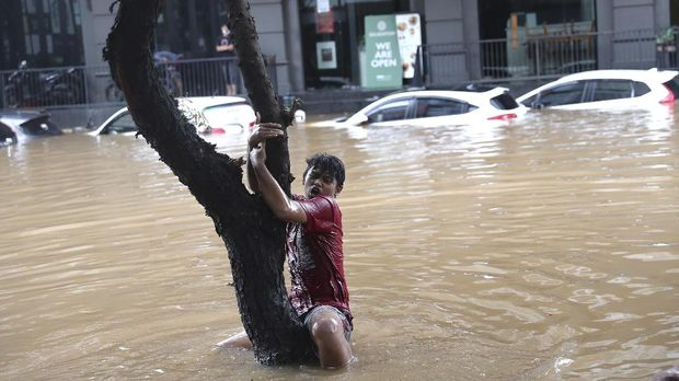 A man grabs a tree to keep from being swept away by flood water through a flooded neighborhood following heavy rains in Jakarta, Indonesia, Saturday, Feb. 20, 2021. Heavy downpours combined with poor city sewage planning often causes heavy flooding in parts of greater Jakarta. (AP Photo/Tatan Syuflana)