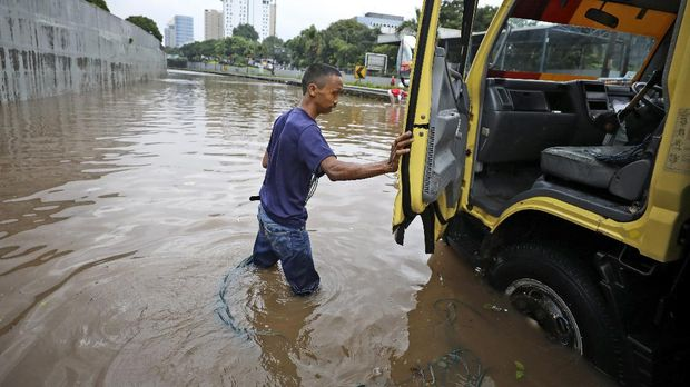 A man steps out of his truck after it was stuck on a flooded toll road following heavy rains in Jakarta, Indonesia, Saturday, Feb. 20, 2021. Heavy downpours combined with poor city sewage planning often causes heavy flooding in parts of greater Jakarta. (AP Photo/Dita Alangkara)