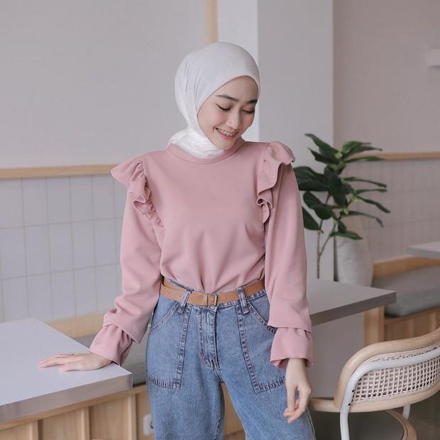 Blus pink dengan ruffle di pundak