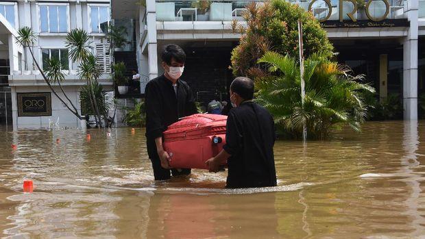 Petugas hotel membawa koper milik tamu saat banjir melanda kawasan Kemang, Jakarta Selatan, Sabtu (20/2/2021). Banjir yang terjadi akibat curah hujan tinggi serta drainase yang buruk membuat kawasan Kemang banjir setinggi 1,5 meter. ANTARA FOTO/Indrianto Eko Suwarso/rwa.