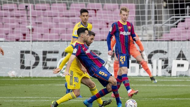 Barcelona's Sergio Busquets, center, controls the ball with Cadiz's Alberto Perea during the Spanish La Liga soccer match between FC Barcelona and Cadiz at the Camp Nou stadium in Barcelona, Spain, Sunday, Feb. 21, 2021. (AP Photo/Joan Monfort)