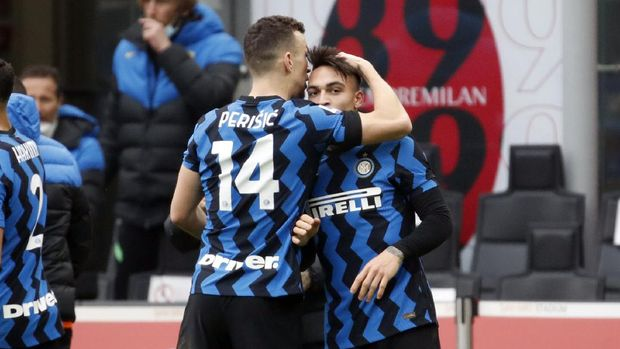 Inter Milan's Lautaro Martinez, right, celebrates with Ivan Perisic after scoring his side's second goal during the Serie A soccer match between AC Milan and Inter Milan, at the Milan San Siro Stadium, Italy, Sunday, Feb. 21, 2021. (AP Photo/Antonio Calanni)