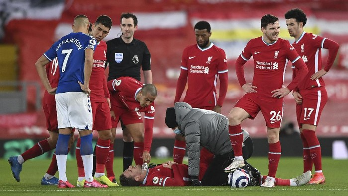 Liverpools Jordan Henderson lies injured on the ground and is attended to by a member of the Liverpool medical team during the English Premier League soccer match between Liverpool and Everton at Anfield in Liverpool, England, Saturday, Feb. 20, 2021. (Lawrence Griffiths/ Pool via AP)