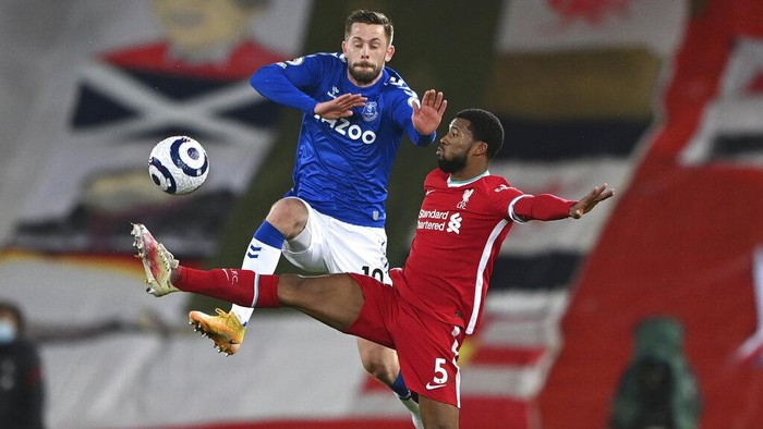 Evertons Gylfi Sigurdsson, leaps as he vies for the ball with Liverpools Georginio Wijnaldum during the English Premier League soccer match between Liverpool and Everton at Anfield in Liverpool, England, Saturday, Feb. 20, 2021. (Lawrence Griffiths/ Pool via AP)
