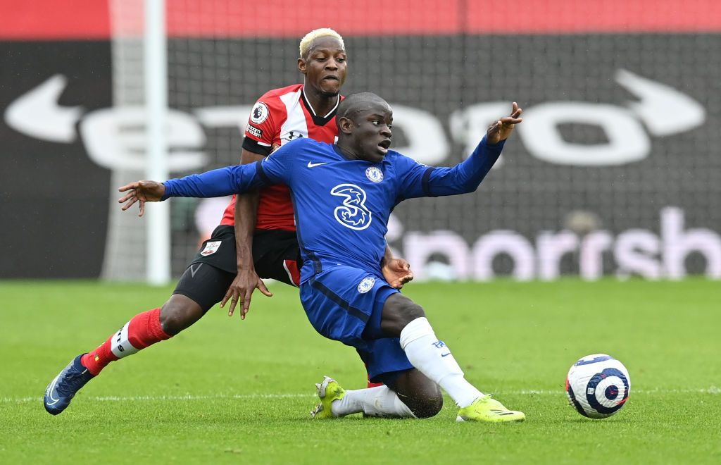 SOUTHAMPTON, ENGLAND - FEBRUARY 20: N'Golo Kante of Chelsea is challenged by Moussa Djenepo of Southampton during the Premier League match between Southampton and Chelsea at St Mary's Stadium on February 20, 2021 in Southampton, England. Sporting stadiums around the UK remain under strict restrictions due to the Coronavirus Pandemic as Government social distancing laws prohibit fans inside venues resulting in games being played behind closed doors. (Photo by Neil Hall - Pool/Getty Images)