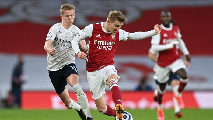 LONDON, ENGLAND - FEBRUARY 21: Martin Odegaard of Arsenal battles for possession with Oleksandr Zinchenko of Manchester City during the Premier League match between Arsenal and Manchester City at Emirates Stadium on February 21, 2021 in London, England. Sporting stadiums around the UK remain under strict restrictions due to the Coronavirus Pandemic as Government social distancing laws prohibit fans inside venues resulting in games being played behind closed doors. (Photo by Shaun Botterill/Getty Images)