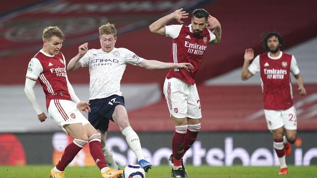 Arsenal's Martin Odegaard, left, and Manchester City's Kevin De Bruyne challenge for the ball during the English Premier League soccer match between Arsenal and Manchester City at the Emirates stadium in London, England, Sunday, Feb. 21, 2021. (John Walton/Pool via AP)