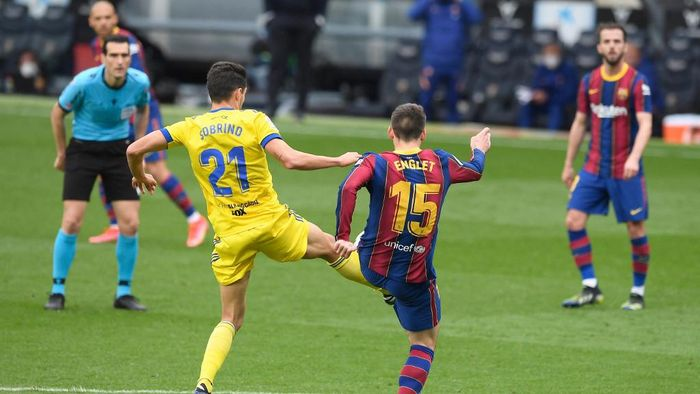Barcelonas French defender Clement Lenglet (R) challenges Cadizs Spanish midfielder Ruben Sobrino during the Spanish league football match between FC Barcelona and Cadiz CF at the Camp Nou stadium in Barcelona on February 21, 2021. (Photo by Josep LAGO / AFP)