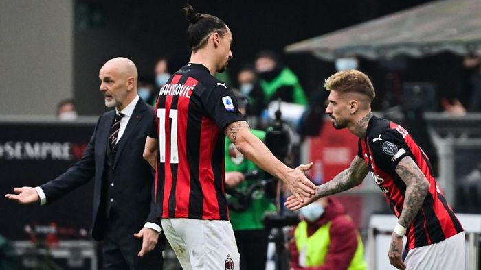 AC Milans Swedish forward Zlatan Ibrahimovic (C) taps hand with AC Milans Spanish forward Samuel Castillejo (R) as he is being substituted by AC Milans Italian coach Stefano Pioli (Rear L) during the Italian Serie A football match AC Milan vs Inter Milan on February 21, 2021 at the San Siro stadium in Milan. (Photo by MIGUEL MEDINA / AFP)