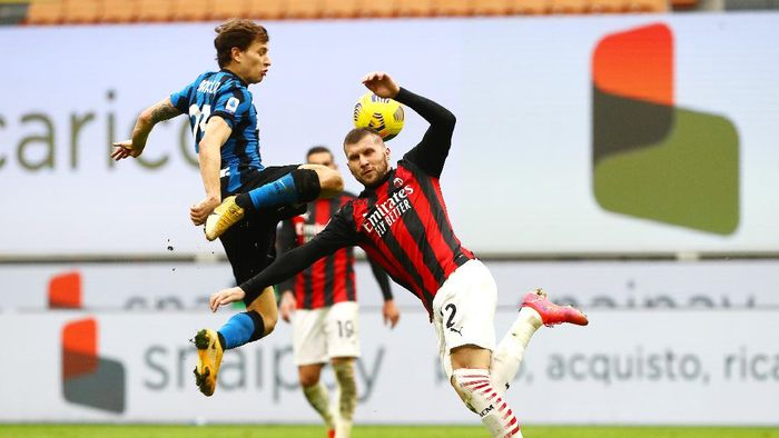 MILAN, ITALY - FEBRUARY 21: Nicolo Barella of FC Internazionale battles for possession with Ante Rebic of AC Milan during the Serie A match between AC Milan and FC Internazionale at Stadio Giuseppe Meazza on February 21, 2021 in Milan, Italy. Sporting stadiums around Italy remain under strict restrictions due to the Coronavirus Pandemic as Government social distancing laws prohibit fans inside venues resulting in games being played behind closed doors. (Photo by Marco Luzzani/Getty Images)
