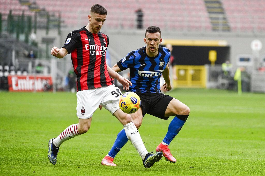 AC Milan's Alexis Saelemaekers, left, and Inter's Ivan Perisic go for the ball during the Serie A soccer match between AC Milan and Inter Milan, at the San Siro Stadium in Milan, Italy, Sunday, Feb. 21, 2021. (Marco Alpozzi/LaPresse via AP)
