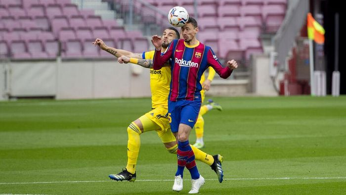 Barcelonas Clement Lenglet, right, jumps for the ball with Cadizs Negredo during the Spanish La Liga soccer match between FC Barcelona and Cadiz at the Camp Nou stadium in Barcelona, Spain, Sunday, Feb. 21, 2021. (AP Photo/Joan Monfort)