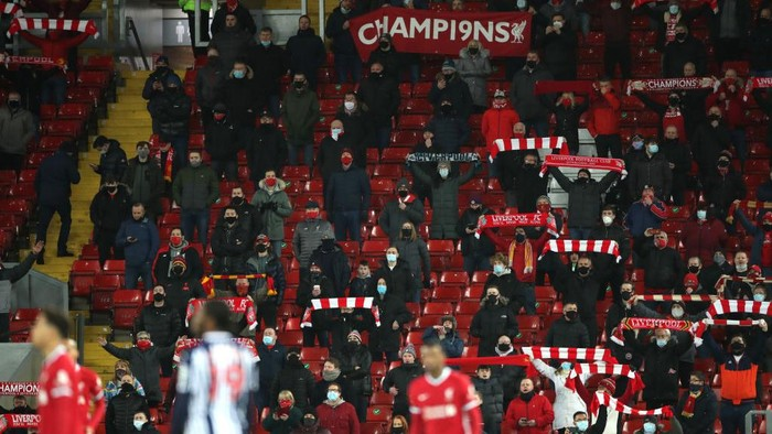 LIVERPOOL, ENGLAND - DECEMBER 27: Liverpool fans sing in their socially-distanced seats during the Premier League match between Liverpool and West Bromwich Albion at Anfield on December 27, 2020 in Liverpool, England. A limited number of fans (2000) are welcomed back to stadiums to watch elite football across England. This was following easing of restrictions on spectators in tiers one and two areas only. (Photo by Nick Potts - Pool/Getty Images)
